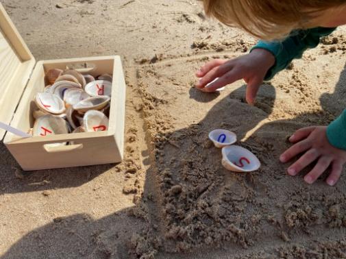 Niño jugando con conchas pintadas con numeros en la arena