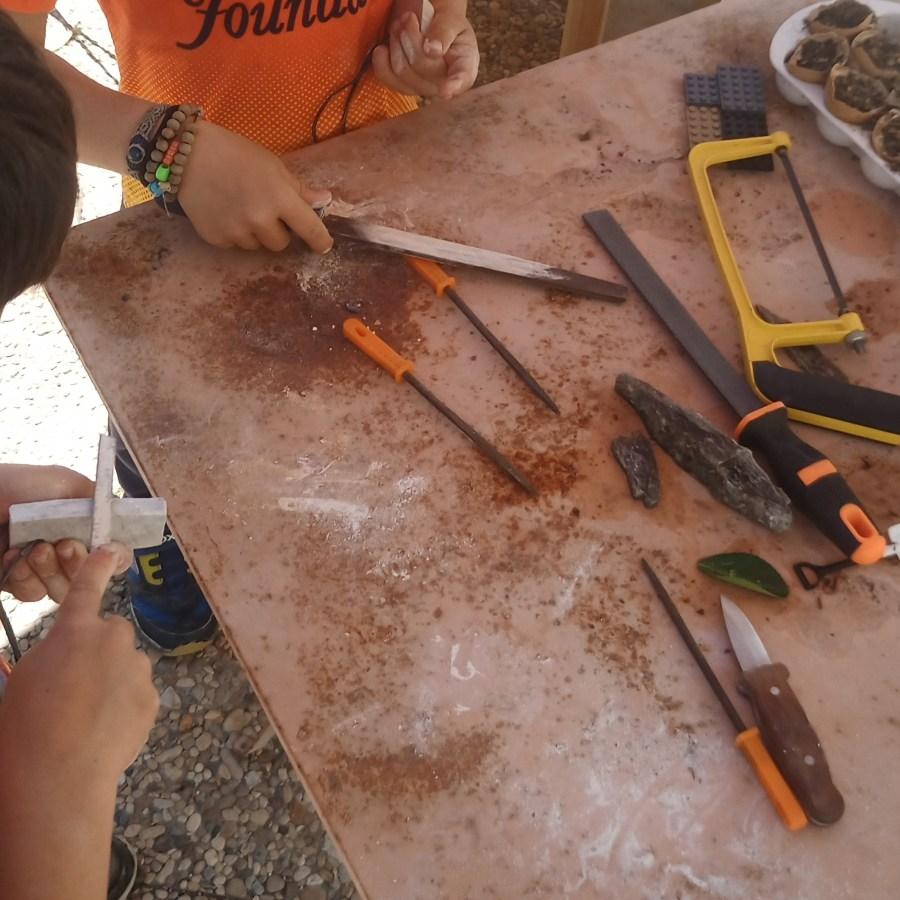 Niños en una mesa con herramientas tallando piedra blanda
