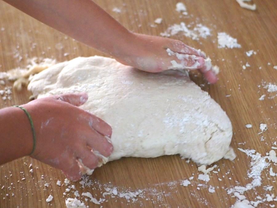 Manos de niño amasando pan