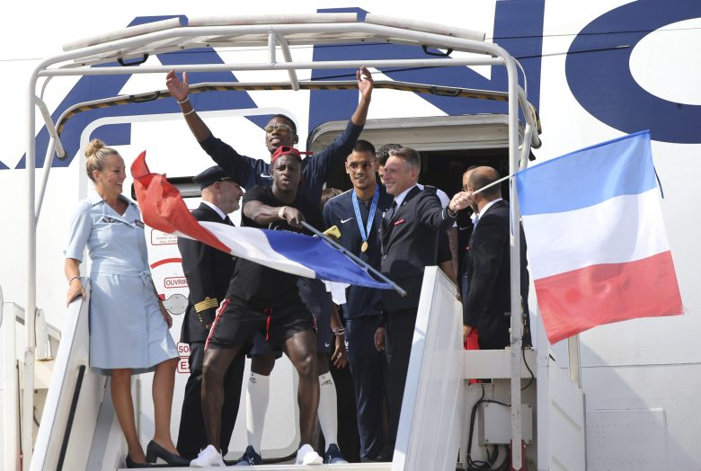 French soccer players exit the plane as the French soccer team arrives at Charles de Gaulle airport, Monday  in Roissy, north of Paris