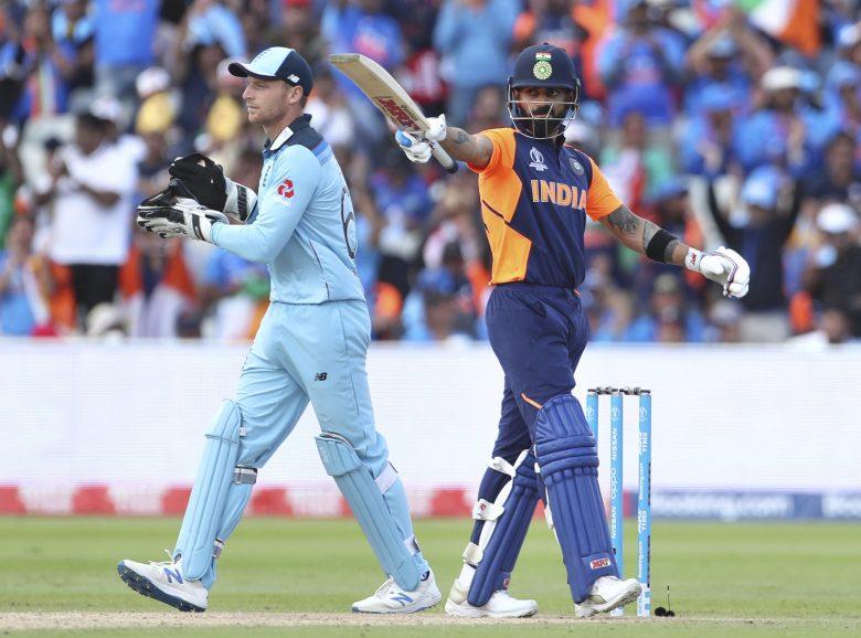 India's captain Virat Kohli, right, raises his bat to celebrate scoring fifty runs