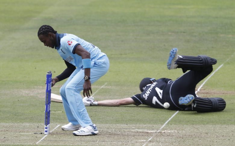 England's Jofra Archer, left fails to collect the ball to run out New Zealand's Mitchell Santner , who is then hit in the back by the ball