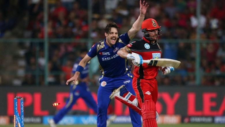 Mumbai Indians' Mitchell McClenaghan, left, celebrates the dismissal of Royal Challengers Bangalore batsman Brendon McCullum