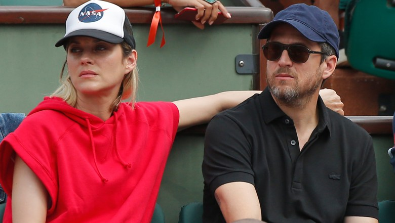 French actress Marion Cotillard and French actor and director Guillaume Canet watch the men's final match of the French Open tennis tournament at the Roland Garros stadium in Paris