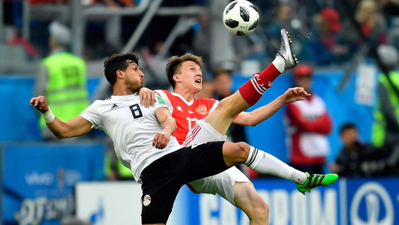 Egypt's Tarek Hamed, left, and Russia's Alexander Golovin compete for the ball during the group A match between Russia and Egypt at the 2018 soccer World Cup in the St. Petersburg stadium in St. Petersburg