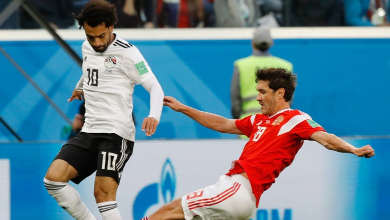 Egypt's Mohamed Salah, left, challenges for the ball with Russia's Yuri Zhirkov during the group A match between Russia and Egypt at the 2018 soccer World Cup in the St. Petersburg stadium in St. Petersburg