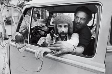 Phil Spector, a small white man with an afro and mustache, is pointing a gun out of a car window, straight at the camera, as a larger man with a beard, helps steady his arm, reaching around him from behind.