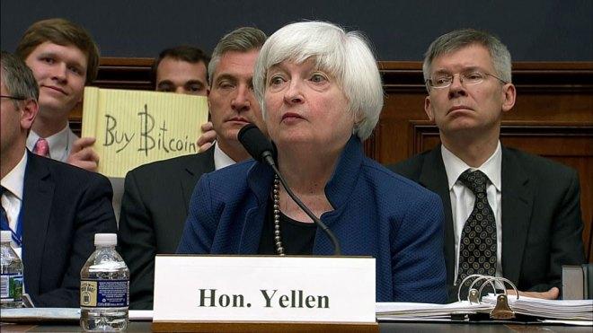 """Durante una de sus comparecencias en 2017, detrás de Yellen, quien califica a la criptomoneda como un activo especulativo, apareció el cartel """"compre Bitcoin""""."""