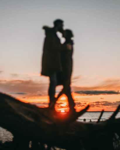faceless couple on coast of sea