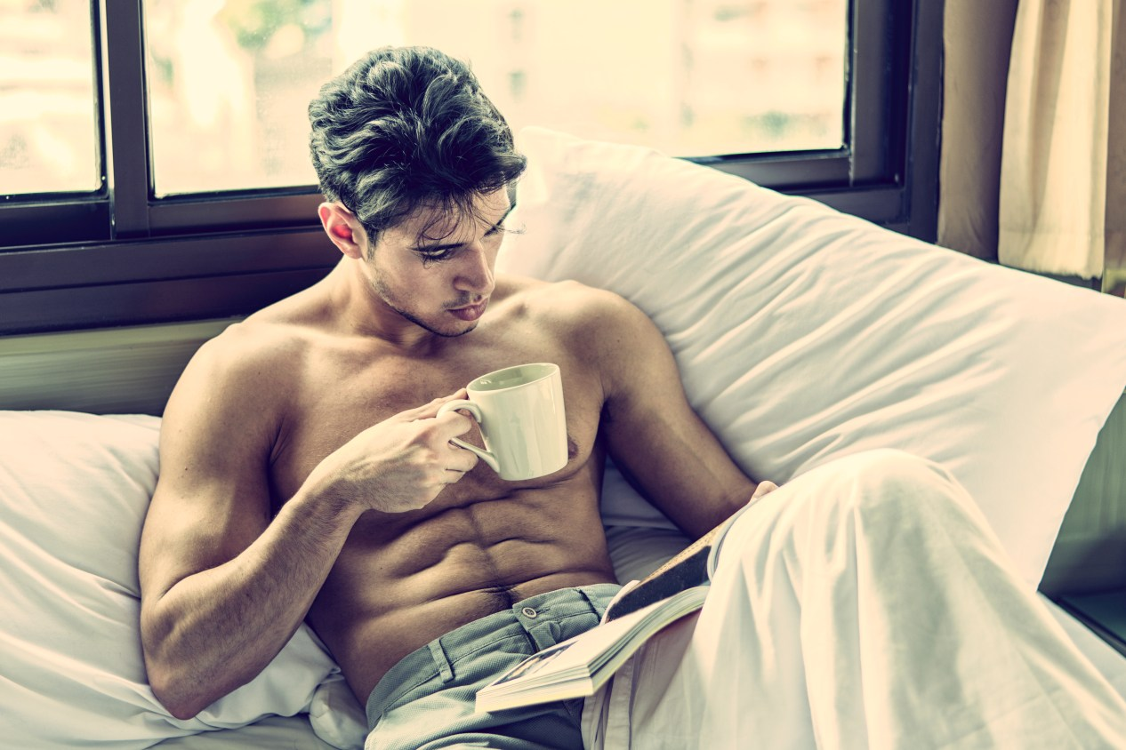 Sexy man reading a book in bed while sipping from a cup of coffee.