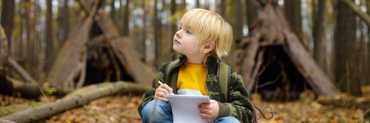 Child with sketch pad sits in clearing