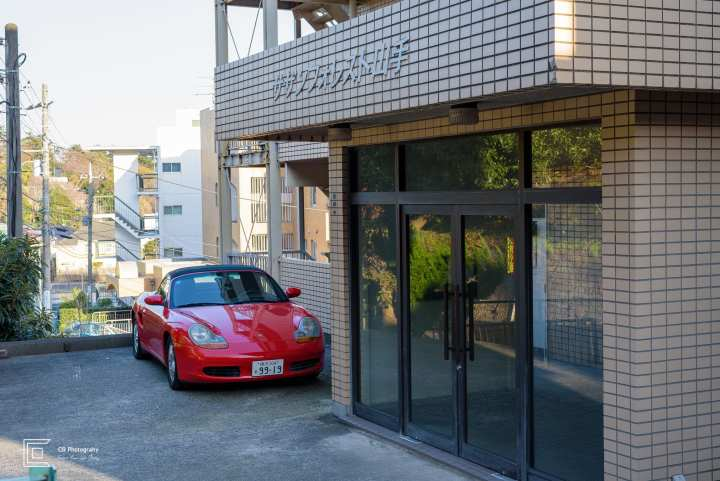 Red Porsche convertible parked in front of a building. Japan. Photography by Cristian Bucur Photographer in Tokyo Metropolitan Area.