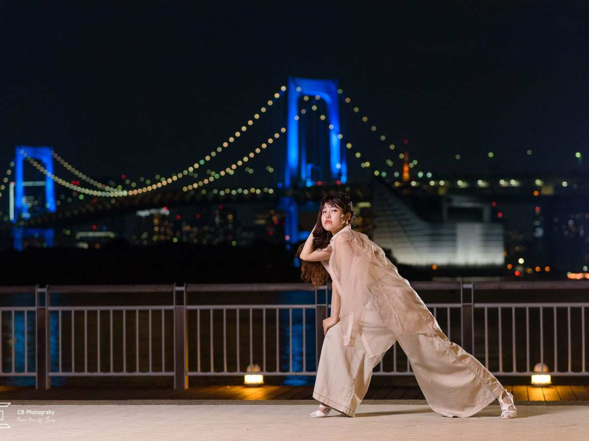 Portrait at night in Odaiba with Rainbow Bridge lit in the background