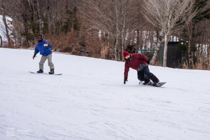 Snowboarders sliding downhill