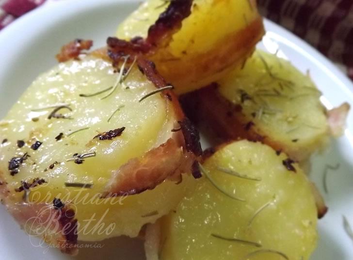 Receita de batata assada preparada com fatias de bacon e alecrim