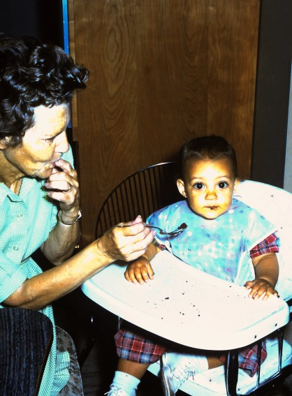 Grandma feeding me in our kitchen