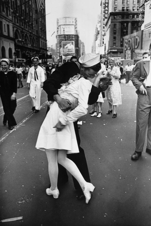 VJ DAY. A jubilant American sailor clutching a white-uniformed nurse in a back-bending, passionate kiss as he vents his joy while thousands jam Times Square  to celebrate the long awaited-victory over Japan.