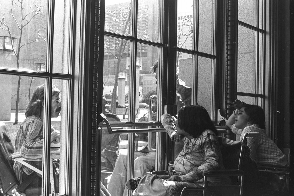 People in wheelchairs inside a building looking out of a glass door, where a man with a wheelchair looks in.