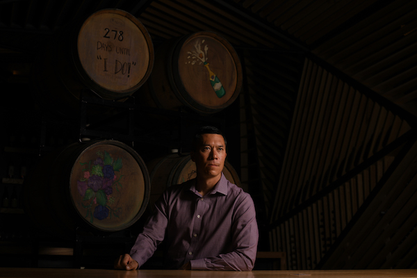 man sitting at wine cellar table in front of wine barrels
