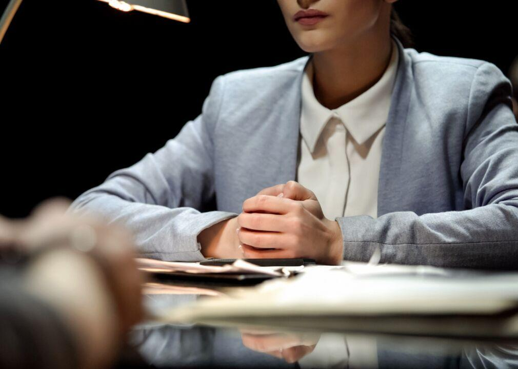 photo of woman sitting at desk with folded hands