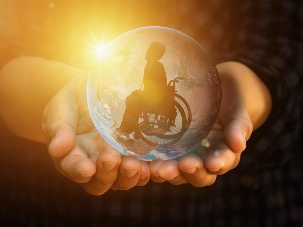 photo of hands holding a globe with photo of wheelchair user inside