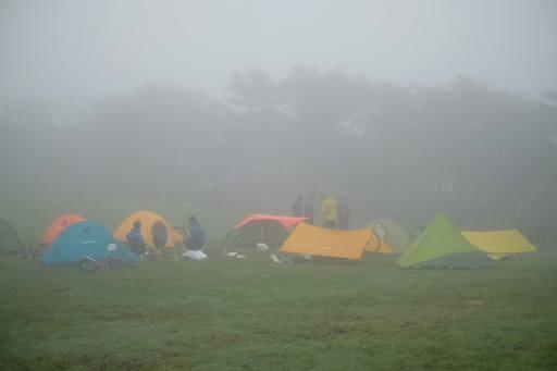 いくつものシェルターと自転車が並ぶ朝のキャンプ場の写真