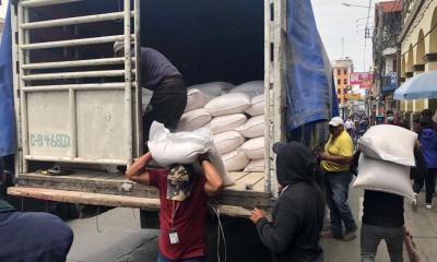 Alcaldes comunitarios cargan con quintales de maíz, donado por el alcalde y algunos concejales, en Totonicapán. (Foto: Carlos Ventura)