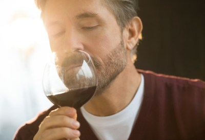 Mature man smelling glass of red wine at home.
