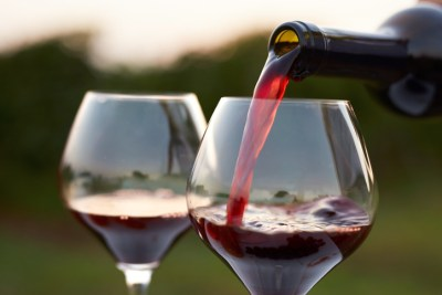 Pouring red wine into glasses in the vineyard at sunset.