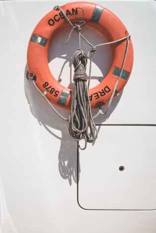lifebuoy and tied rope hanging in yacht