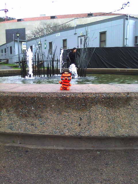 amigurumi crochet tiger by a water fountain