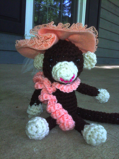Georgina the crochet monkey sitting on the front porch awaiting a mint julep