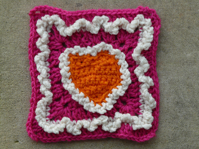Pink crochet square with an orange heart and white ruffles