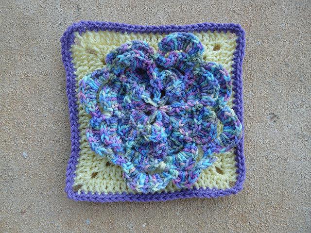 Crochet granny square with large crochet flower appliqué