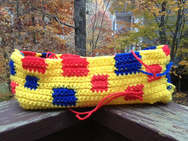 A yellow crochet purse with red and blue accents