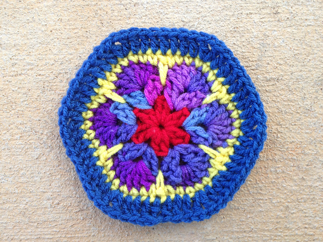 An African flower crochet hexagon with a blue suede border