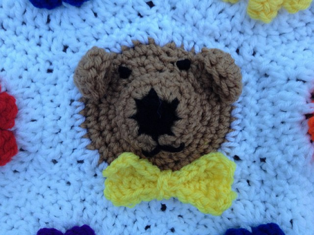 A bear crochet hexagon with a crochet bow