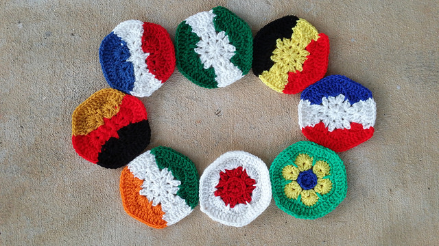 Group photo of crochet hexagons for a crochet soccer ball inspired by the flags of eight of the participating countries