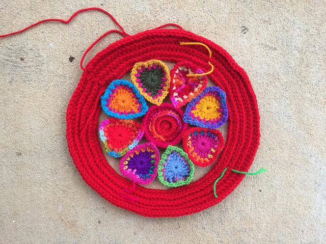 a crochet ring around a motif of boho crochet hearts