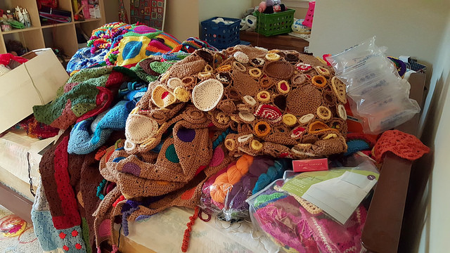 a pile of crochet blankets