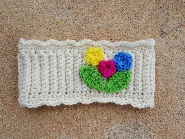 A completed crochet earwarmer/headband with crochet flowers awaiting February flurries