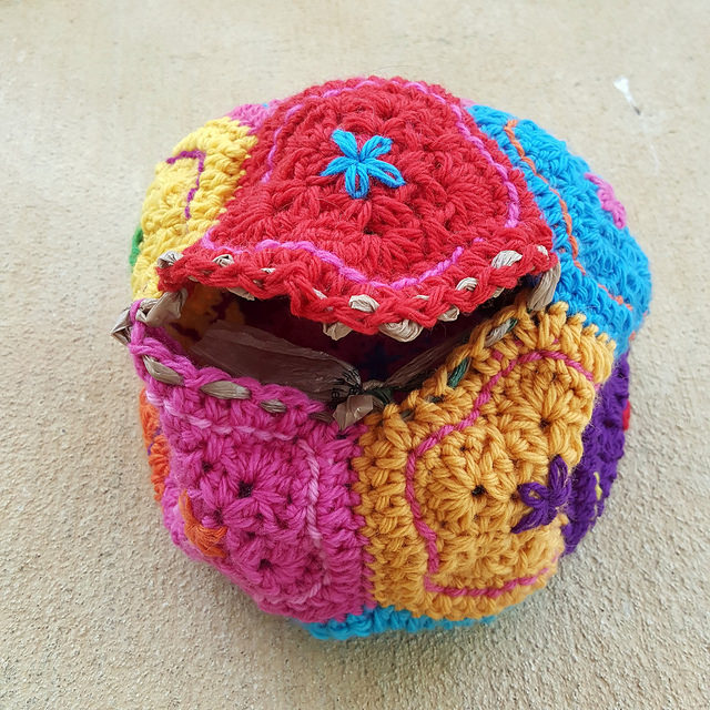 a strand of plastic woven through the stitches of a crochet dodecahedron in preparation for felting