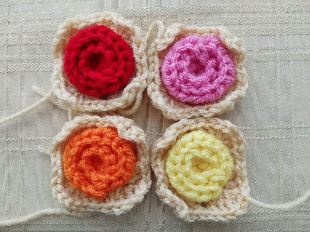 Four granny squares with crochet rose centers ready to be joined