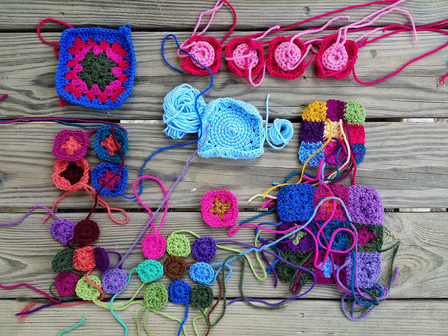 more than thirty crochet remnants ready to become nine rehabbed crochet squares and granny squares