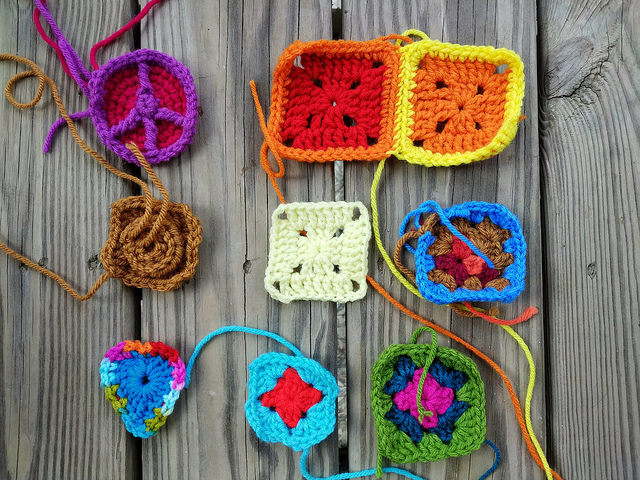 Nine assorted crochet remnants in need of crochet square rehab
