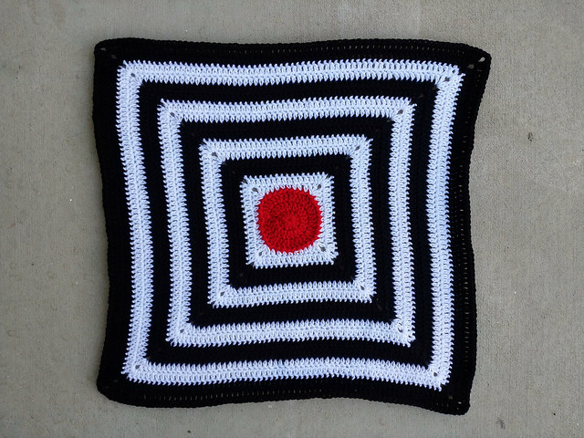 A red crochet circle centered black and white stripe baby blanket with a half double slip stitch border