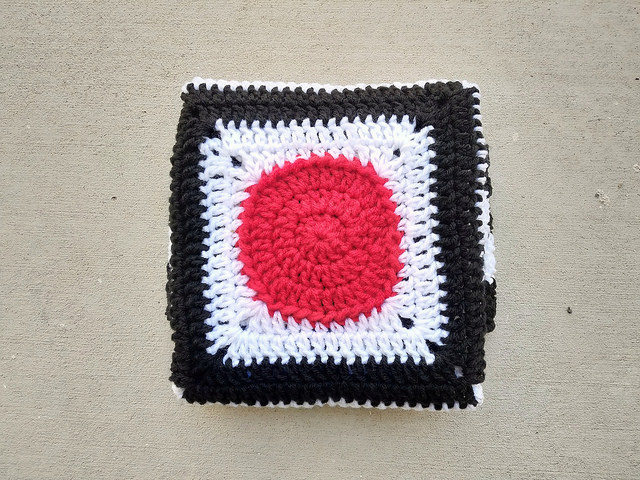 a new kind of baby blanket made with red, white, and black yarn