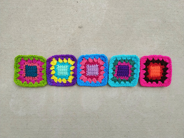 Five crochet remnants waiting to become five-inch crochet squares