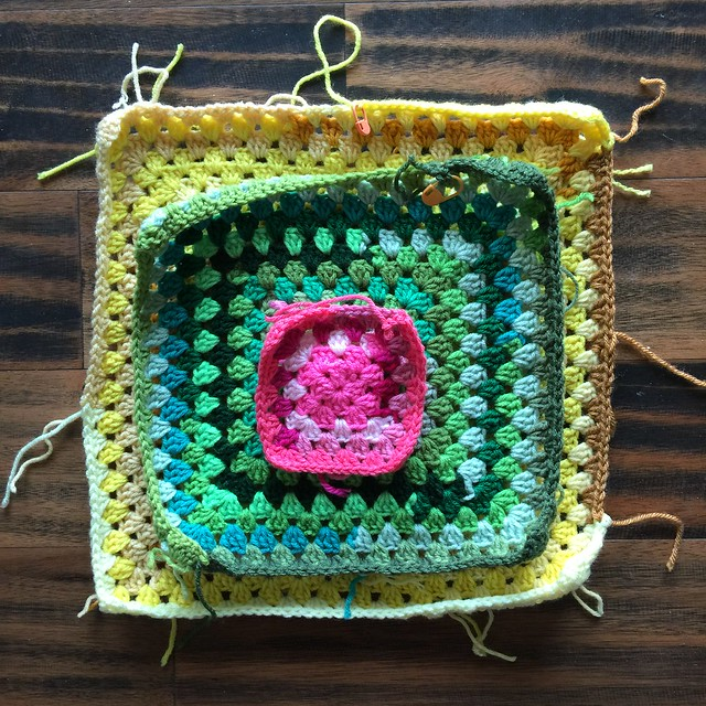 Three scrap yarn granny squares with the pink scrap yarn square on top