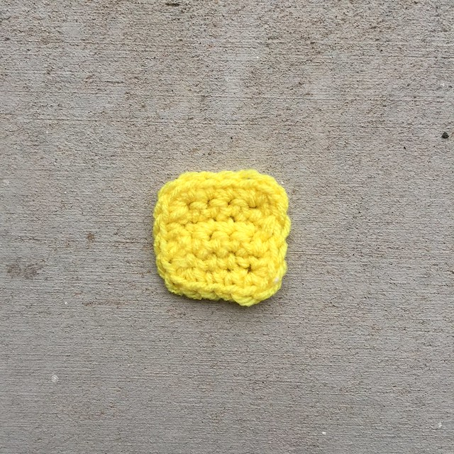 A yellow square that is crochet ghost of Christmas past